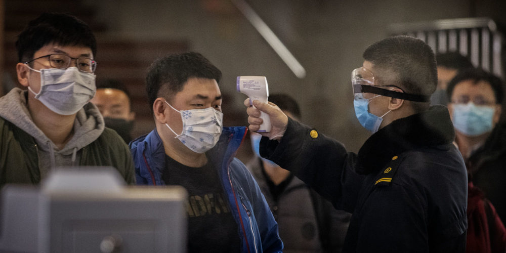 A Chinese passenger that just arrived on the last bullet train from Wuhan to Beijing is checked for a fever by a health worker at a Beijing railway station on January 23, 2020 in Beijing, China. (Photo: Kevin Frayer/Getty Images)